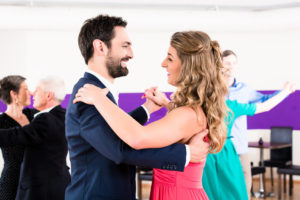 Young and senior couples getting dance lessons