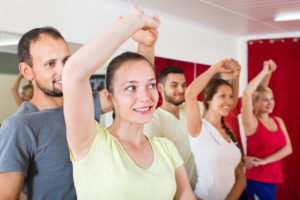 Smiling adults dancing the bachata together at dance studio