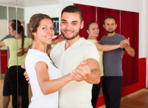 Smiling young couple enjoying of partner dance in dance class